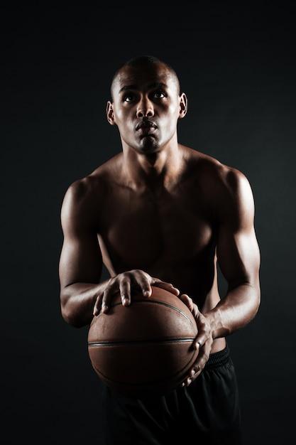 Portret dat van jonge afro-amerikaanse basketbalspeler, bal voorbereidingen treft te werpen Gratis Foto
