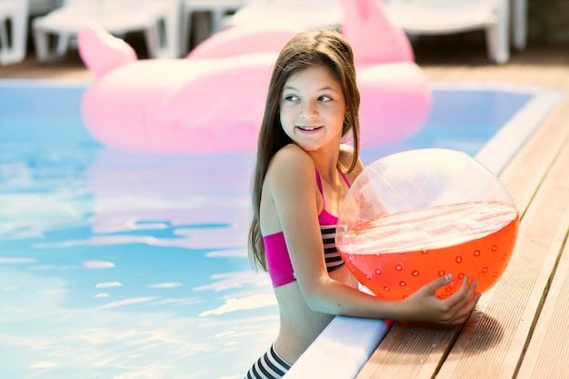 Portret dat van meisje een strandbal houdt weg kijkend Gratis Foto