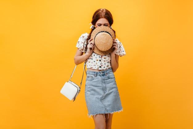 Portret dat van ondeugend meisje haar gezicht behandelt met strohoed. dame gekleed in een lichte denim rok en bloemenprint top poseren op een oranje achtergrond. Gratis Foto