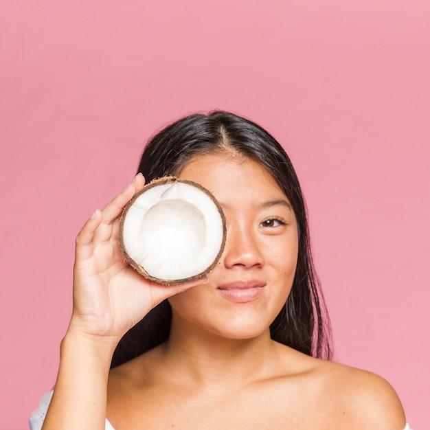 Portret dat van smileyvrouw een kokosnoot houdt Gratis Foto