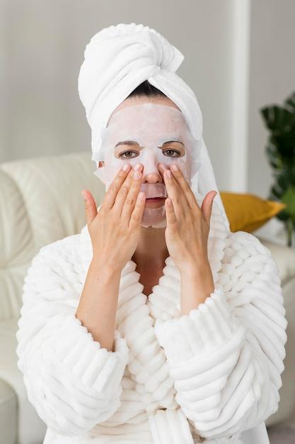 Portret dat van vrouw gezichtsmasker toepast Gratis Foto