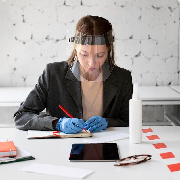 Portret dat van vrouw met gezichtsschild werkt Gratis Foto