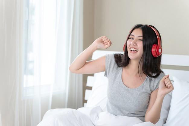 Portret dichte omhoog mooie tienervrouw die rode bluetoothhoofdtelefoon dragen Gratis Foto