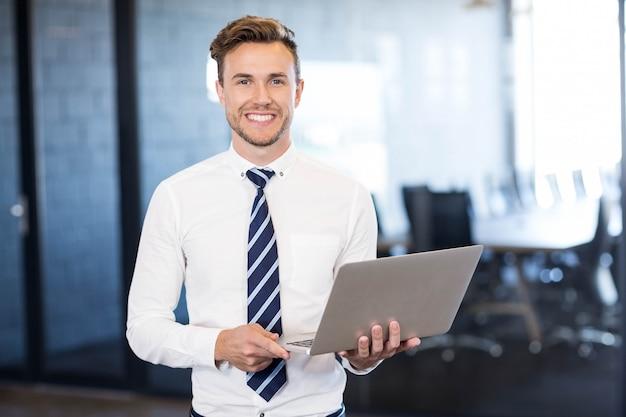 Portret die van de bedrijfsmens zich met laptop vooraan conferentieruimte bevinden in bureau Premium Foto