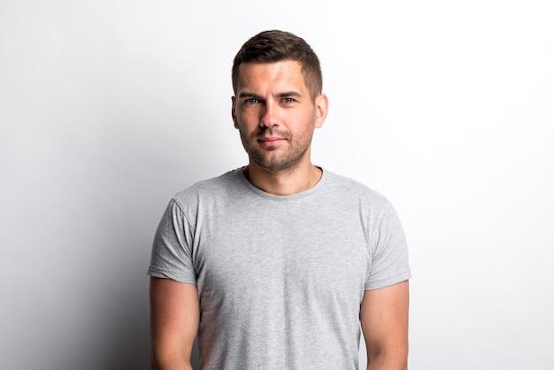 Portret die van de charmante jonge mens zich tegen op witte achtergrond bevinden Gratis Foto