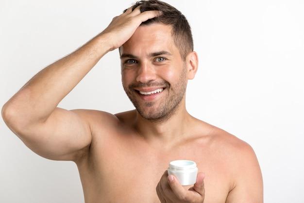 Portret die van de gelukkige mens haarwas toepassen die zich tegen witte achtergrond bevinden Gratis Foto