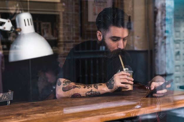 Portret die van de jonge mens de chocolademelk drinken die mobiele telefoon in koffie met behulp van Gratis Foto