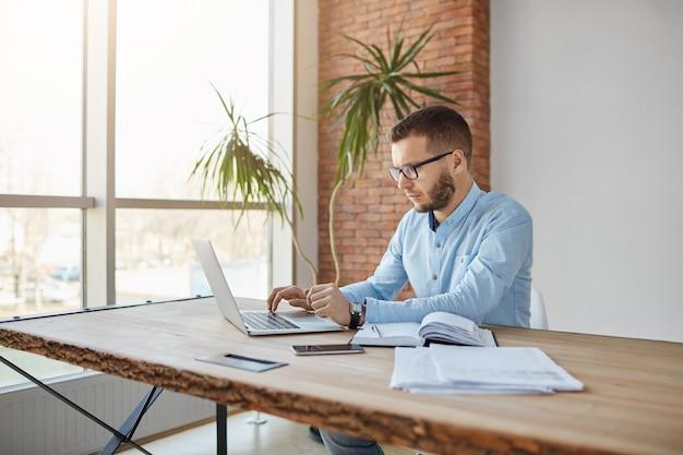 Portret die van de volwassen ernstige mannelijke zitting van de bedrijfdirecteur in comfortabel bureau zitten, bedrijfwinsten op laptop controleren Gratis Foto