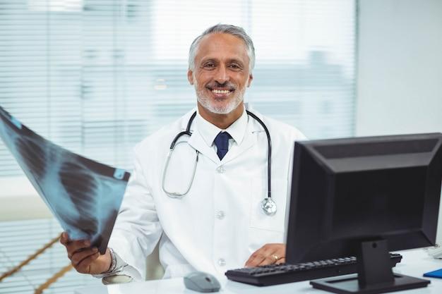 Portret die van gelukkige arts x-ray in kliniek houden Premium Foto