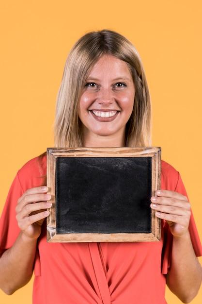 Portret die van glimlachende vrouw lege zwarte lei houden Gratis Foto