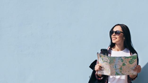 Portret die van het glimlachen van de kaart van de vrouwenholding zich tegen blauwe muur bevinden die weg eruit zien Premium Foto