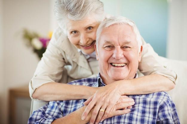 Portret die van hogere vrouw de mens in woonkamer omhelzen Premium Foto