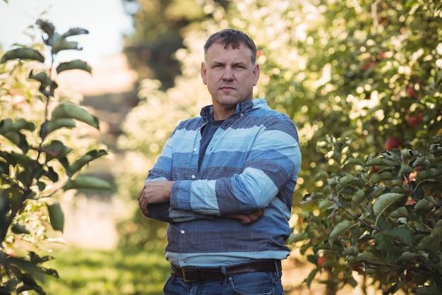 Portret die van landbouwer zich met die wapens bevinden in appelboomgaard worden gekruist Gratis Foto