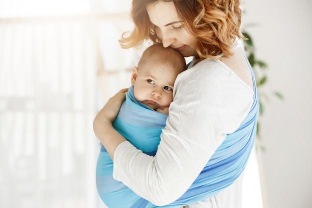 Portret die van mooie jonge moeder haar pasgeboren babyjongen met liefde en zorg strak houden. ze glimlacht en voelt het geluk van de moedermomenten. Gratis Foto
