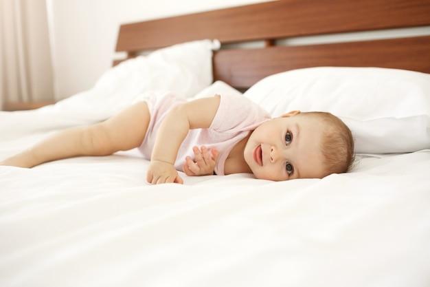 Portret die van mooie leuke pasgeboren baby tong tonen die thuis op bed liggen. Gratis Foto