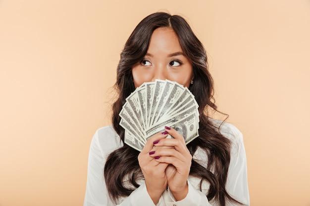 Portret die van succesvolle aziatische vrouw mond behandelen met ventilator van 100 dollarsrekeningen die over salaris of inkomen het stellen zijn tevreden over beige achtergrond Gratis Foto