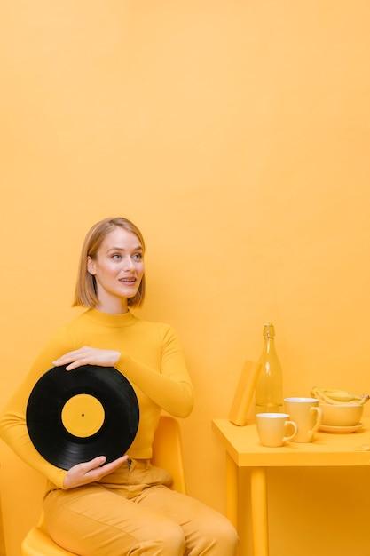 Portret die van vrouw een vinyl in een gele scène houden Gratis Foto