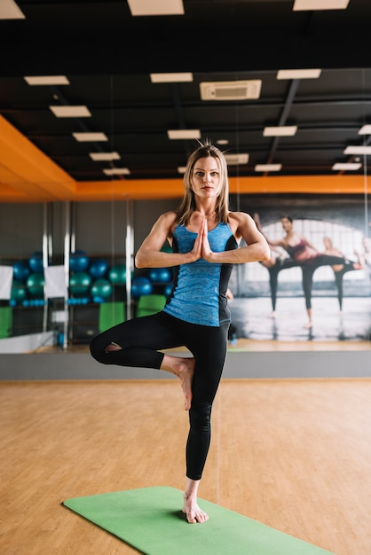Portret die van vrouw zich in yoga het stellen bij gymnastiek bevinden Gratis Foto
