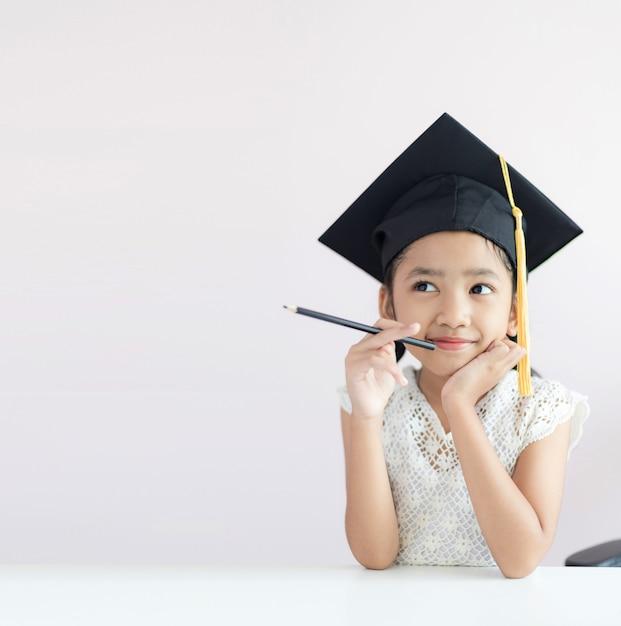 Portret draagt weinig aziatisch meisje gediplomeerde het potloodzitting die van de hoedenholding iets denken en met geluk glimlachen Premium Foto