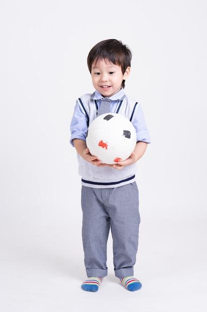 Portret een kleine jongen die zich met ter beschikking het glimlachen van voetbal bevinden Gratis Foto