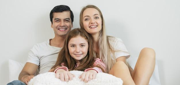 Portret gelukkige familie het besteden tijd samen aan bed in slaapkamer. Premium Foto