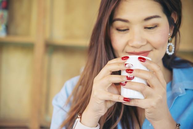 Portret gelukkige jonge aziatische dame in koffiewinkel Gratis Foto
