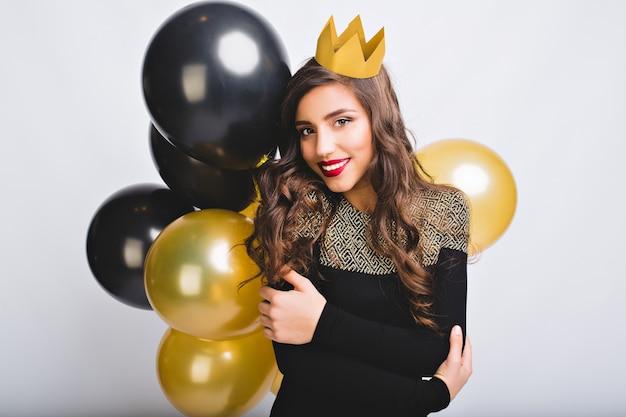 Portret geweldig mooi meisje met lang krullend donkerbruin haar, gele kroon, zwarte en gouden ballonnen op witte ruimte. Gratis Foto