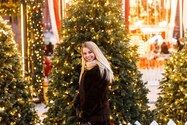 Portret in volle groei, russische mooie vrouw in een nerts jas op het rode plein in moskou in de kersttijd Premium Foto