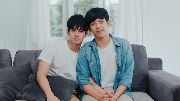 Portret jong aziatisch vrolijk paar die thuis gelukkig het glimlachen voelen. de aziatische lgbtq-mensen ontspannen toothy glimlach kijkend aan camera terwijl thuis het liggen op bank in woonkamer in de ochtend. Gratis Foto