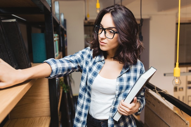 Portret jonge aantrekkelijke brunette vrouw in zwarte bril in bibliotheek op zoek naar boeken. slimme student, studietijd, goed werk, academisch. Gratis Foto