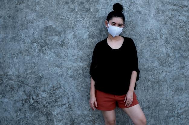 Portret jonge aziatische vrouw die dragend een masker Premium Foto