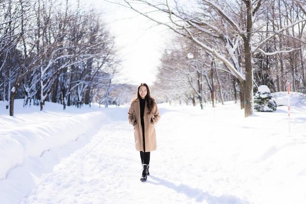 Portret jonge mooie aziatische vrouw glimlach gelukkig reizen en genieten met sneeuw winterseizoen Gratis Foto