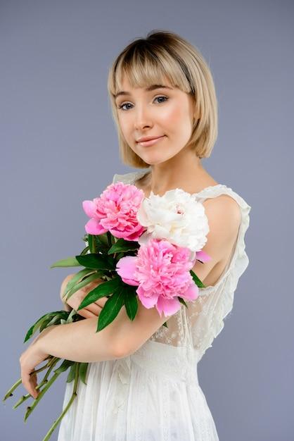 Portret jonge vrouw met boeket bloemen over grijze backgro Gratis Foto