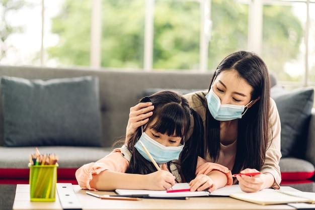 Portret liefde aziatische familie moeder en klein aziatisch meisje leren en schrijven in boek met potlood huiswerk maken in quarantaine voor coronavirus beschermend masker dragen met sociale afstand nemen thuis Premium Foto