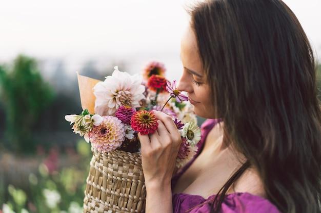 Portret meisje met lang haar met een bloemmand. loop door de bloementuin. meisje en bloemen. floristiek. Premium Foto