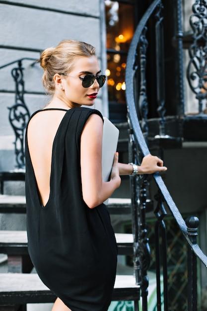 Portret mooi model in zwarte korte jurk met blote rug op trappen buiten. ze kijkt naar beneden. Gratis Foto