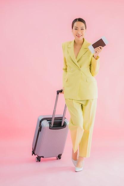 Portret mooie jonge aziatische bedrijfsvrouw met bagagezak en paspoort op kleur Gratis Foto