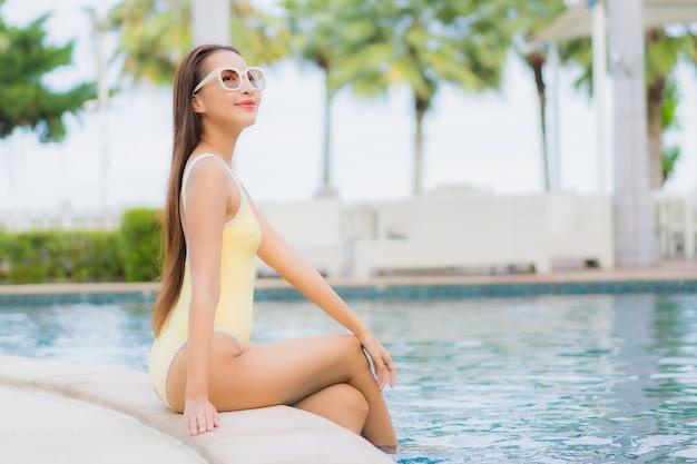 Portret mooie jonge aziatische vrouw buiten ontspannen in zwembad in vakantiereis Gratis Foto