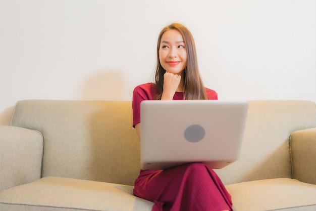 Portret mooie jonge aziatische vrouw die computerlaptop op bank in woonkamerbinnenland met behulp van Gratis Foto