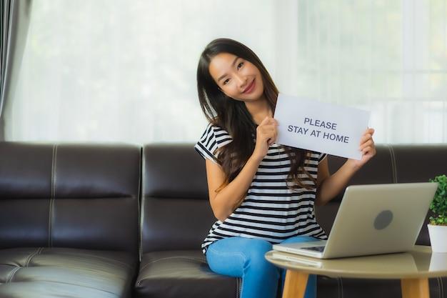 Portret mooie jonge aziatische vrouw die laptop of computer noterbook op bank met het conceptenwerk van huis gebruiken Gratis Foto