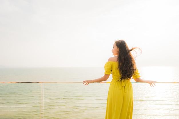 Portret mooie jonge aziatische vrouw glimlach gelukkig en ontspannen op buiten balkon met zee strand en oce Gratis Foto
