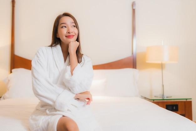 Portret mooie jonge aziatische vrouw glimlacht ontspannen op bed in slaapkamer interieur Gratis Foto