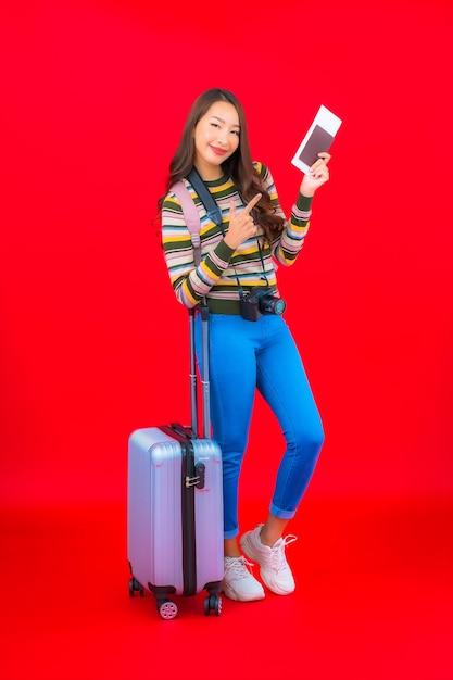 Portret mooie jonge aziatische vrouw met bagage en instapkaart op rode muur Gratis Foto