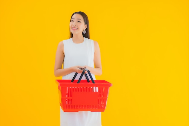 Portret mooie jonge aziatische vrouw met boodschappenmand om te winkelen bij de supermarkt Gratis Foto