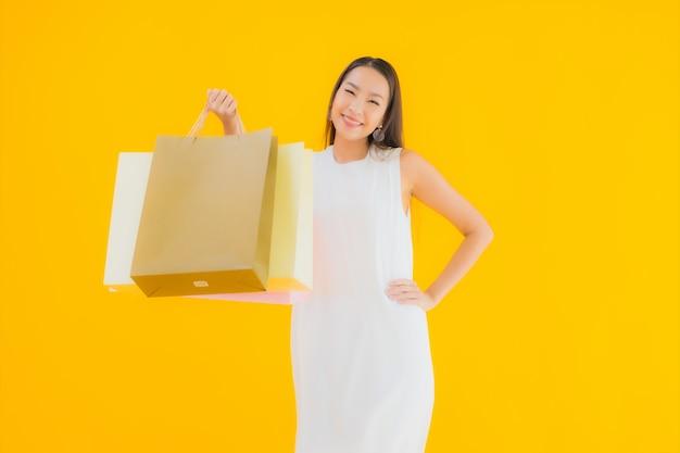 Portret mooie jonge aziatische vrouw met boodschappentas van warenhuis verkoopt Gratis Foto