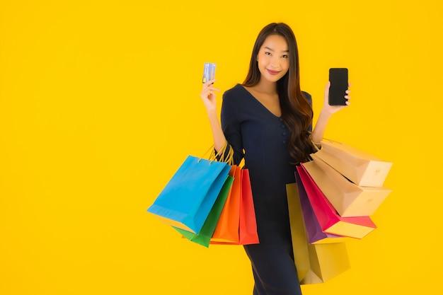 Portret mooie jonge aziatische vrouw met boodschappentas Gratis Foto