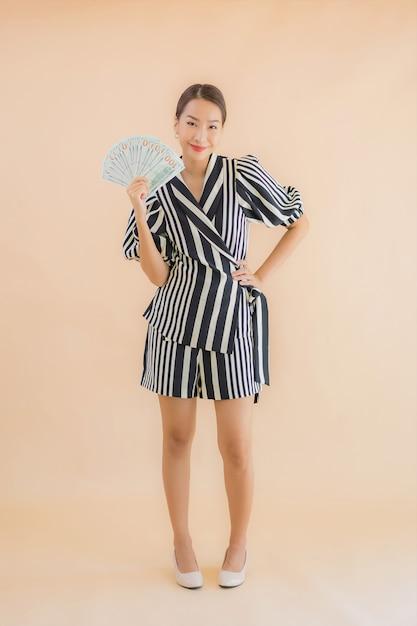 Portret mooie jonge aziatische vrouw met contant geld en geld Gratis Foto