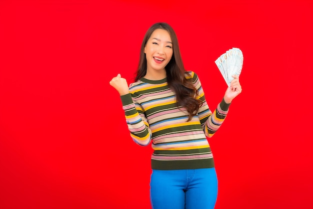 Portret mooie jonge aziatische vrouw met contant geld en mobiele telefoon op rode muur Gratis Foto