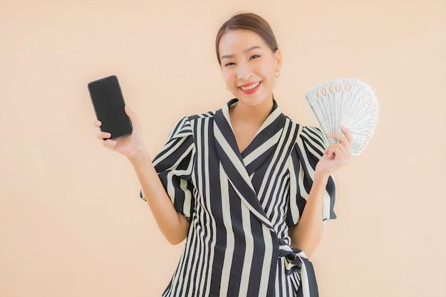Portret mooie jonge aziatische vrouw met contant geld en slimme mobiele telefoon Gratis Foto
