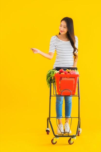 Portret mooie jonge aziatische vrouw met de mand van de kruidenierswinkelmand van supermarkt in winkelcomplex Gratis Foto
